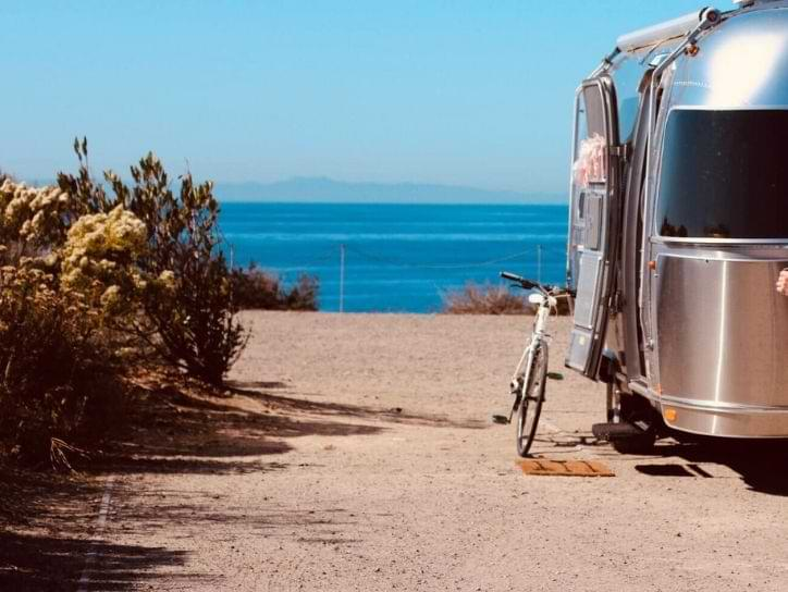 Airstream travel trailer standing on river bank